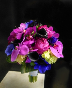 Sumptuous Jewel-toned bridal bouquet featuring phalaenopsis orchids, anemone, peonies, and callas.